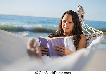 Content woman lying on hammock reading book on the beach