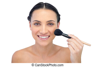 Smiling natural model applying makeup on her face on white...