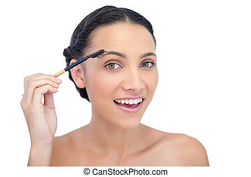 Surprised young brunette using eyebrow brush on white...