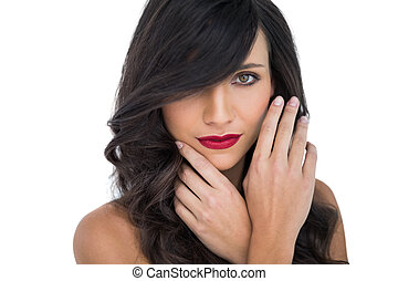 Glamorous brunette with red lips posing touching her face