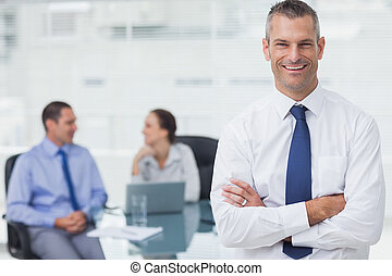 Smiling businessman posing crossing arms in bright office