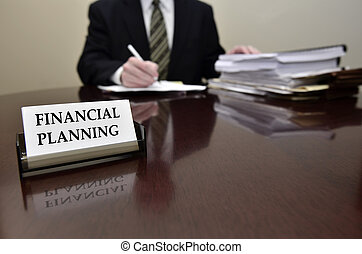 Financial Planning - Man sitting at desk holding pen papers...