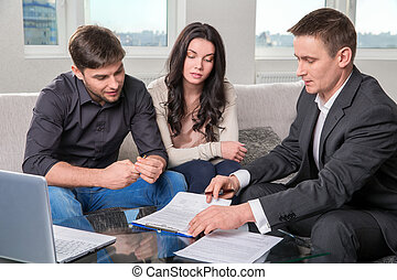 Agent advises the couple, signing documents - couple...