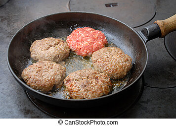 Frying hamburger - Hamburgers in a frying pan one raw