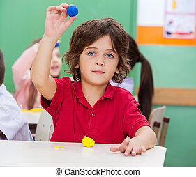 Boy Showing Clay In Classroom