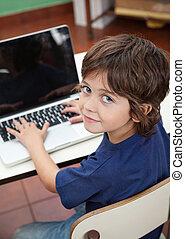 Little Boy With Laptop In Preschool - Portrait of cute...
