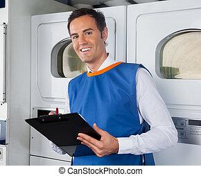 Male Helper Writing On Clipboard In Laundry - Portrait of...