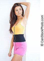 Sexy brunette girl in mini skirt posing against white wall