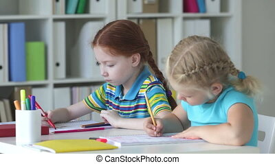 Classmates - Little blonde girl drawing with enthusiasm, her...