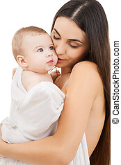 mother kissing adorable baby - family, parenting and child...