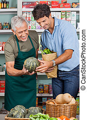 Salesman Assisting Male Customer In Shopping Vegetables -...