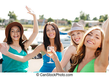 girls with champagne glasses on boat - summer holidays and...