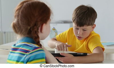 School friends - Boy using a digital tablet, girl watching...