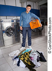 Man Holding Empty Basket With Dirty Clothes On Floor -...