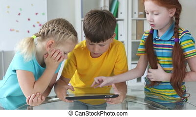 Modern kids using a touchpad sitting together