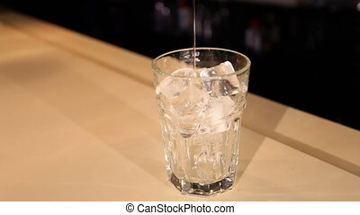 View of bartender pours liquor into glass with ice