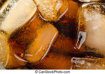 Ice in coke glass - Ice cubes floating in a glass of coke