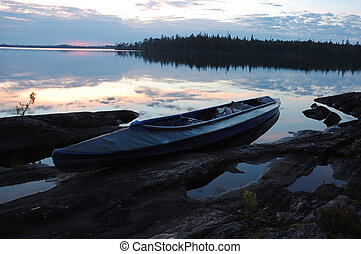 Canoe at stone bank of Engozero lake,Polar Karelia, Russia