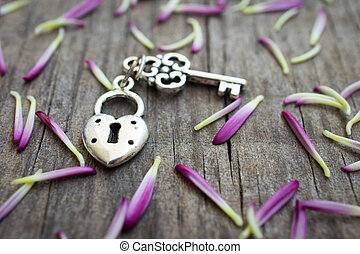 Key with heart shaped lock charm on wooden background.