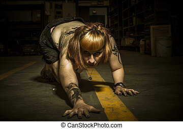 Danger, sensual woman in an industrial building