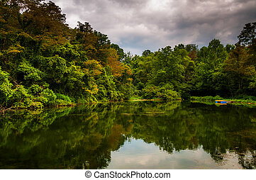 Trees and storm clouds reflecting in a pond in York County, Pennsylvania.