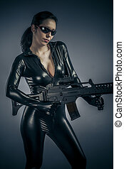 Airsoft guard, police woman holding a big gun, latex costume