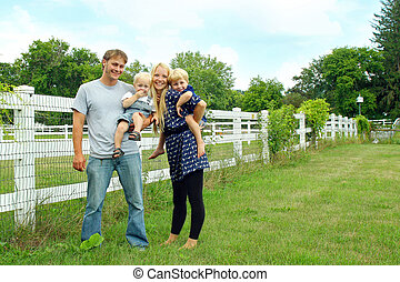Happy Family Outside by White Fence - a happy, attractive...
