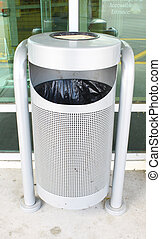 A metal trash/cigarette disposal bin bolted to the concrete to keep it from being stolen outside a business