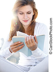 Delightful young woman reading a bo
