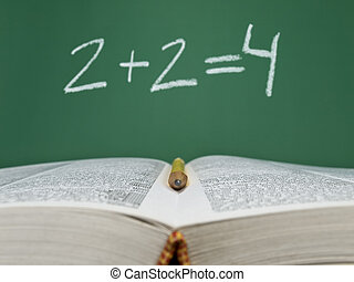 Basic sum - 2 + 2 = 4 written on a chalkboard with an open...
