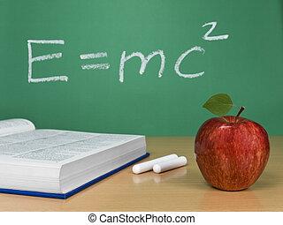 E=mc2 - Einstein´s formula on a chalkboard with an apple, a...