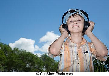 teenager in ear-phones - The teenager in ear-phones listens...