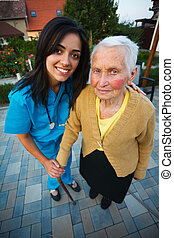 Nurse with Elderly Woman - Kind caring doctor holding an...