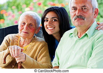 Nurse with Seniors - Young kind nurse welcoming the visitor...