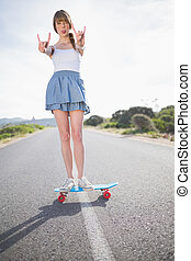 Trendy woman making rock and roll gesture while balancing on her skateboard on a deserted road