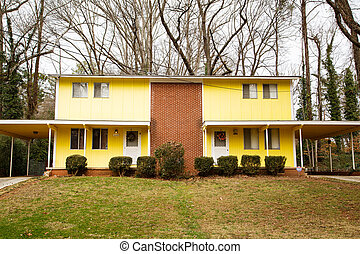 Duplex of Brick and Yellow Siding - A small duplex with...