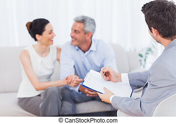 Couple speaking while salesman is holding contract on couch...
