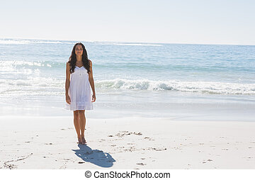 Beautiful brunette in white sun dress walking from the ocean...