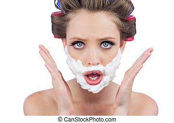 Astonished woman posing with shaving foam on face on white...