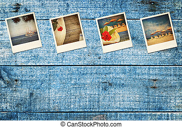 Old worn vacation polaroid pictures, on blue wooden decking