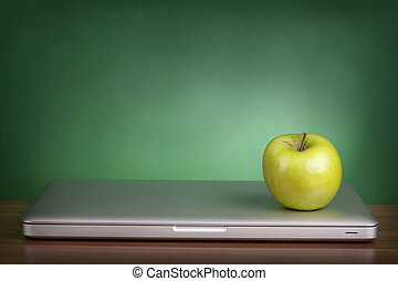 Laptop and green apple