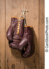 Boxing Gloves hanging against an old wood wall