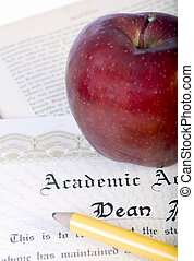 Graduation - A red apple and pencil lay on top of a diploma