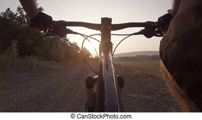 Riding mountain bike at sunset - Cyclist riding mountain...