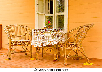Cozy veranda with wicker garden furniture in a traditional...