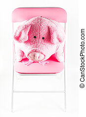 pink fabric pig is on a chair