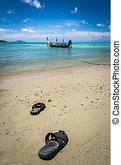 pair of sandal on the beach with a fishing boat under blue...