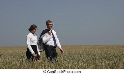 Business field - Business people walking across the field in...
