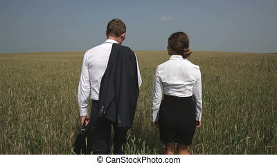 Cultivated land - The rear-view of a business team going...