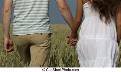 Rural romance - Romantic young people holding hands walking...